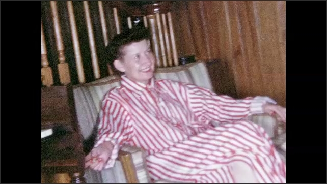 1950s: UNITED STATES: man in pyjamas smiles at camera. Lady and man in matching night gowns. Lady smokes cigarette