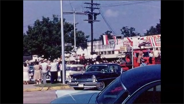 1950s: Sparkling parade float with girls in formal dresses atop it. Liberty Chamber of Commerce car. People watch on street. Woman on horseback in parade. Red truck drives down parade route.