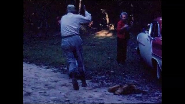 1950s: Grey-haired woman holds 3 dead squirrels by their tails. Man jokingly chases another man with an axe.