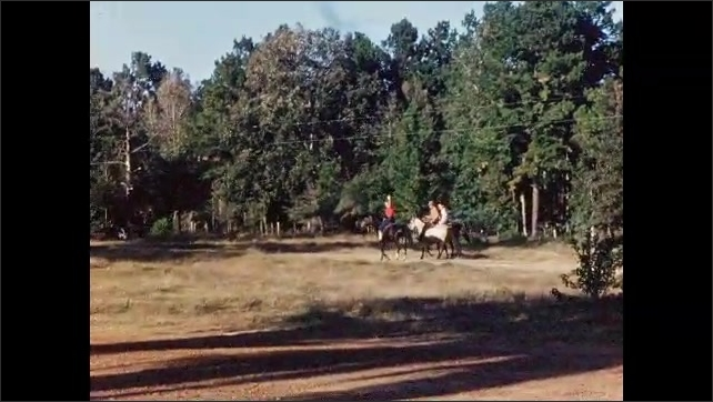 1950s: Three people ride horses into the forest.