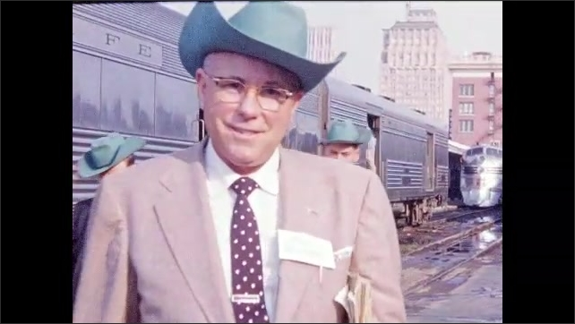 1950s: People in cowboy hats, suits, and nametags on railway platform. Group tours Henry Ford Greenfield Village museum, including sign marking Hermitage Slave Quarters.