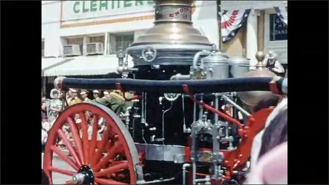 1950s: Majorette in bearskin hat twirls baton. Marching band. Horse-drawn fire engine driven by an African-American man. Marching band. Eight team horse carriage.