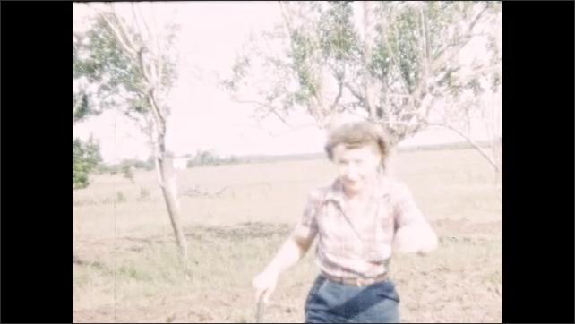 1950s: UNITED STATES: lady runs across garden. Lady picks up stick. Lady runs towards camera. Man drives tractor