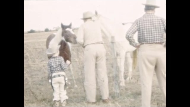 1950s: UNITED STATES: man and boy stand in field. Boy dressed as cowboy. Family stroke horses in field. Boy in cowboy costume points gun at camera