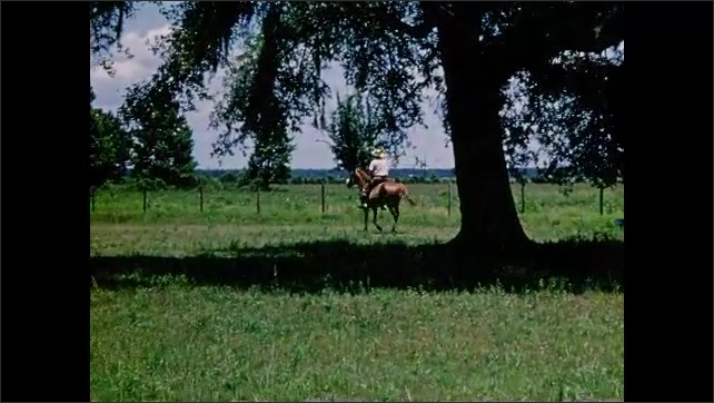 1950s: UNITED STATES: man rides horse in field. Car by field