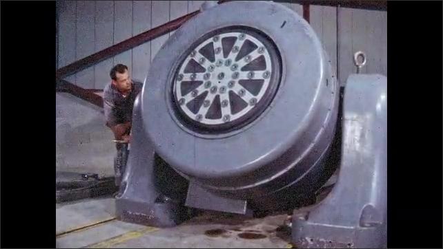 1960s: Engineer in laboratory cranks handle and lowers large metal generator.