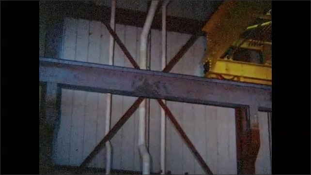 1960s: Factory suspension crane moves slowly along metal tracks in workshop rafters.