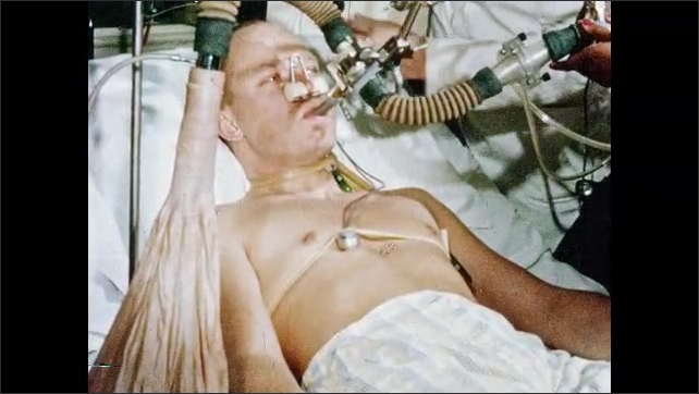 1970s: Scientist adjusts computer near test subject. Astronaut lies in bed and breaths through test apparatus. Scientist looks at stopwatch and speaks.