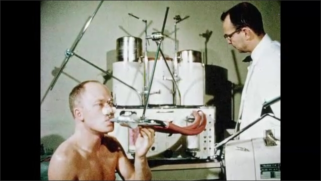1970s: Man breathes into tubes and monitor cylinders move up and down. Doctor monitors breathing machine. Scientists physically examine test subject in bed.