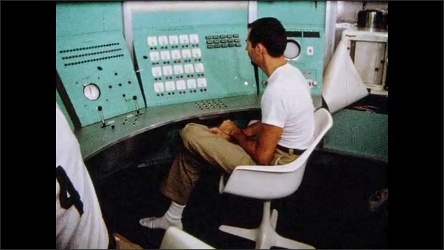 1970s: Men monitor test subjects from video control console. Test subjects push buttons at command console.
