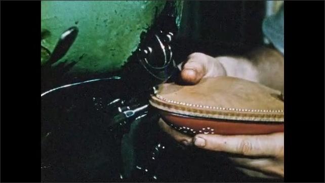 1950s: Man uses machine to trim sole of shoe. Man uses stitching machine to stitch sole onto shoe.