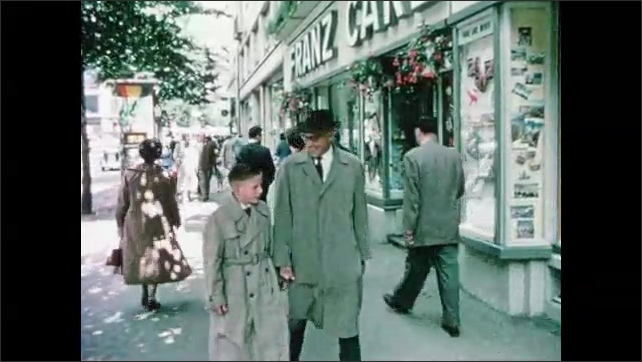 1960s: signs hang from building feature a lion, goat and three kings. car drives down curvy road near water. man and boy in trenchcoats walk on sidewalk, stop and stare at window display of crossbows.