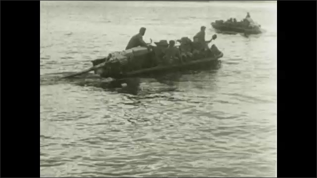 1930s: Soldiers in field launch grenades. Soldiers on bridge with tanks. Soldiers on boats.