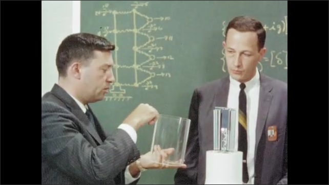 1960s: Man writes equation on chalkboard, walks over to model rocket, removes top. Men examine model satellite, talk.