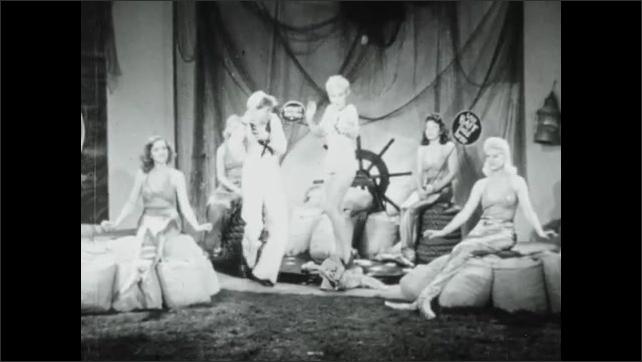 1940s: Sailor sits down next to mermaid, smiles. Mermaid woman stands up, smiles, drops mermaid tail, walks away, dances. Man follows woman.