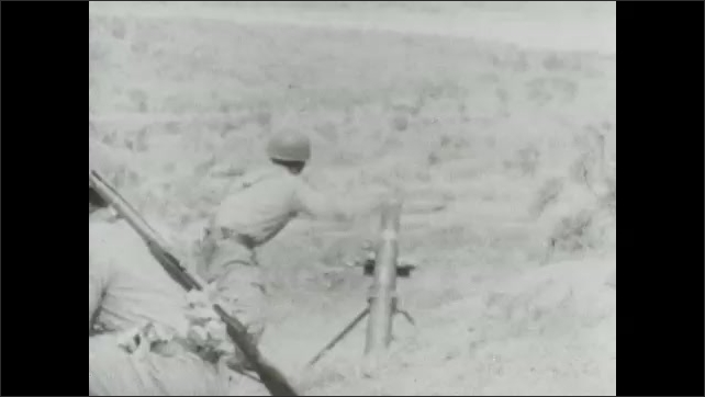 1940s: Soldiers load mortars, shoot guns. Soldiers advance through smokey field.