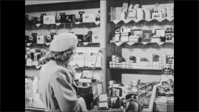 1940s: Store.  Woman and store employee speak.  Woman picks up wallet and hands to man.  Man approaches woman.