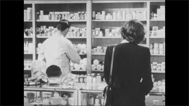 """1940s: Store.  Man and woman stand at counter.  Men hands product to woman.  Man looks at display and opens jar.  People talk.  Book titled """"SELL AS CUSTOMERS LIKE IT."""""""