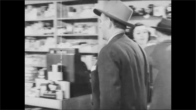 1940s: Store.  Man approaches counter and speaks to salesman.  Man buys object.  Man gestures.  Man walks to back of store.  Men have conversation.