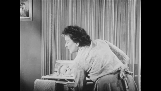 1940s: Girl combs hair and complains.  Woman changes baby's diaper.  Woman speaks.