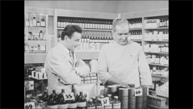 1940s: Store.  Boy knocks down pyramid of products by pulling out middle piece.  Men turn and laugh.  Boy runs away.  Men speak.