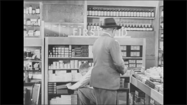 1940s: UNITED STATES: man in pharmacy talks to customer. Man shows product to customer. Man opens box.