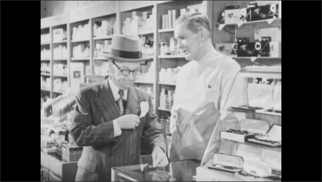 1940s: UNITED STATES: man shows product to customer in shop. Man buys pencil leads in store. Men talk at shop counter