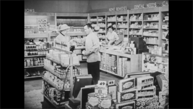 1940s: UNITED STATES: lady give hat to man. Man helps customer in store. Lady at shop counter asks advice