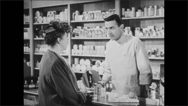 1940s: UNITED STATES: man serves lady at counter in store. Man talks to difficult customer. Lady shows product to man at counter