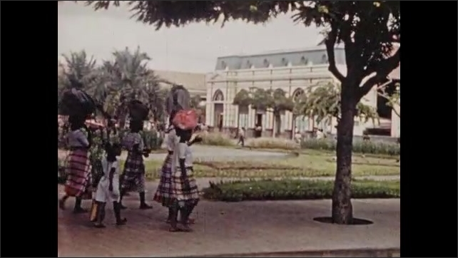 1940s South Africa: Trolley leaves station.  City.  Sculpture in town square.  Young women walk with loads on heads.