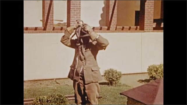 1940s South Africa: Man gathers handfuls of snakes.  Man puts snakes on top of hat.