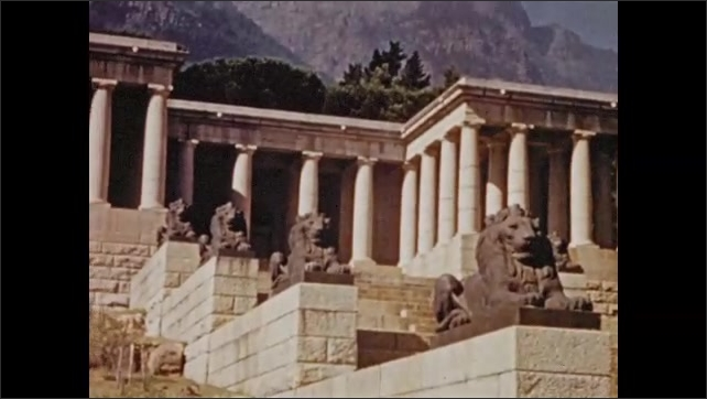 """1940s South Africa: Caption describes the """"Rhodes' Memorial.""""  Statues.  Building with columns.  Text reads """"GROOTE SCHUUR.""""  Mansion."""