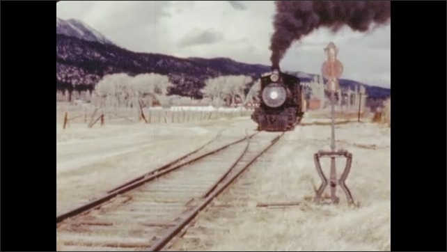 1940s: Mountains.  Train rolls down tracks.