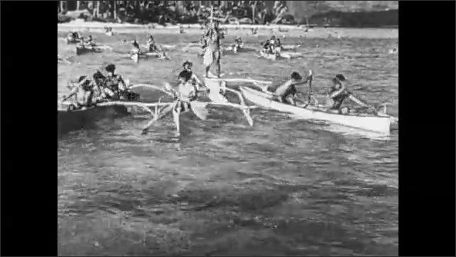 1930s: Fleet of canoes leaves tropical beach.  People row boats.