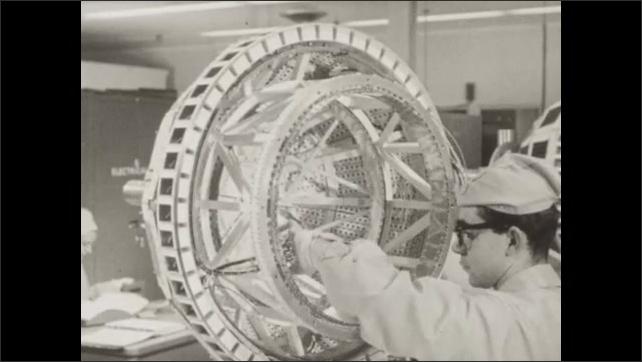 1960s: Flag waves near laboratory building. Men works on Telstar satellite. Man speaks near satellite.
