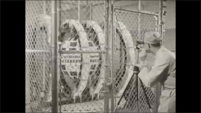 1960s: Telstar satellite spins in gyroscopic machine behind chain-link fence. Man films satellite spinning in cage. Men work at communication consoles. Rocket stands at launchpad.