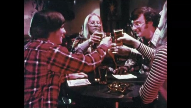 1970s: Club.  Young people sit at table.  People sing.  People pick up beers and drink.  Young man pushes up on woman's cup.  Girl gulps and widens eyes.