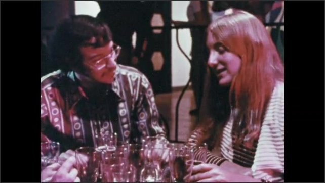 1970s: Dance club.  Young people sit at table.  Young man grabs woman's hair and hugs her.  People smile and talk.