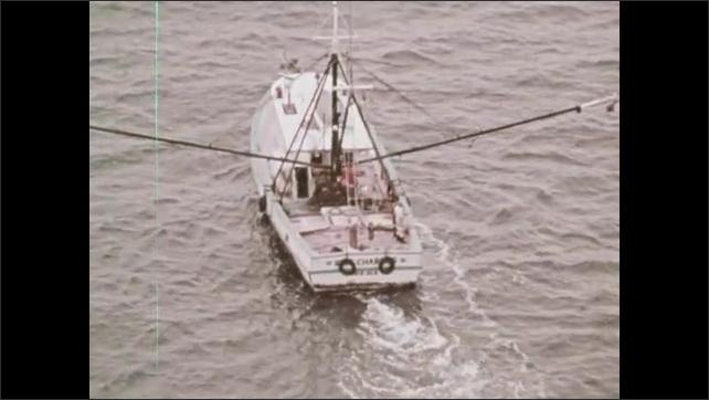 1970s: Oil platforms in ocean. Shrimp boat on water.