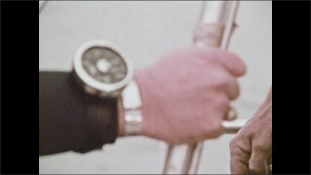1970s: Man sharpens metal point on spear. Man examines point, talk, laughs. Man loads up speargun. Men put on scuba gear.