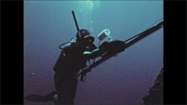 1970s: Men hold up scale with fish attached. Scuba diver cocks spear gun, swims under oil platform.