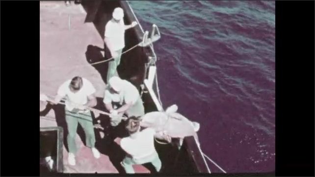 1970s: People fish off of boat next to oil platform. People pull fish onto boat. Shrimp boat travels across water.