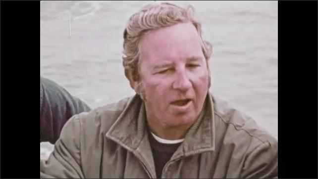 1970s: Men stand on boat, talk. Man cuts open fish.