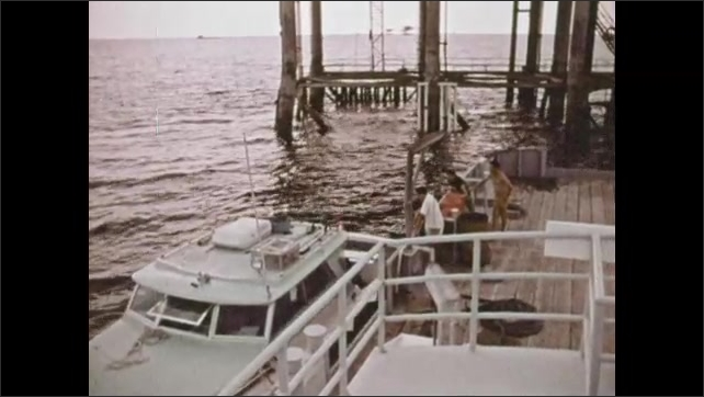 1970s: Scuba diver hunts barracuda, spears barracuda. Boat docks next to larger boat, Man hands fish up to man on larger boat. Men sit around table, man brings out fish on platter.