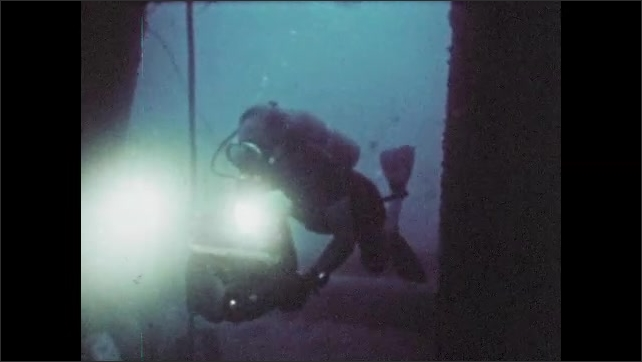 1970s: Scuba diver shines light through water, fish swim about.