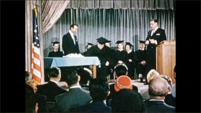 1950s: Graduation ceremony.  Man hands graduate diploma.  Boy drops and picks up paper.  Men shake hands.  People clap.