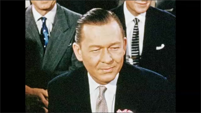 1950s: Men sit in audience.  Man smiles and thinks.