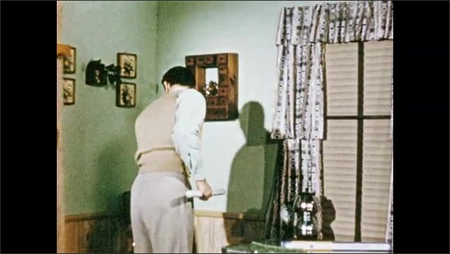 1950s: House.  Man stands on chair to change light bulb.  Man falls.