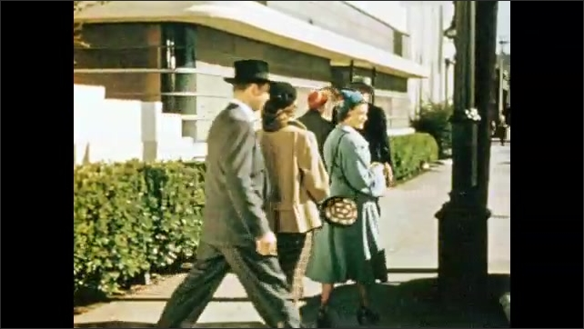 1950s: Man smiles and shrugs.  Church.  Family walks to car.  Man approaches and greets people.  Men run.