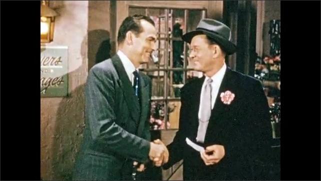 1950s: Men stand outside flower shop and talk.  Man holds photograph.  Men shake hands.  Man walks away.